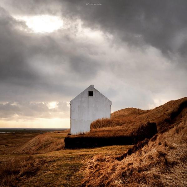 Dette er fra sør Island. Et gammelt hus i stort landskap. Typisk øyeblikk når sola bryter igjennom på en regnværsdag. Det var den enkle geometriske husgavlen i kontrast til det myke landskapet som først fanget interessen. Typisk eksempel på bilde som har forandret stemning fra opptak til endelig resultat.