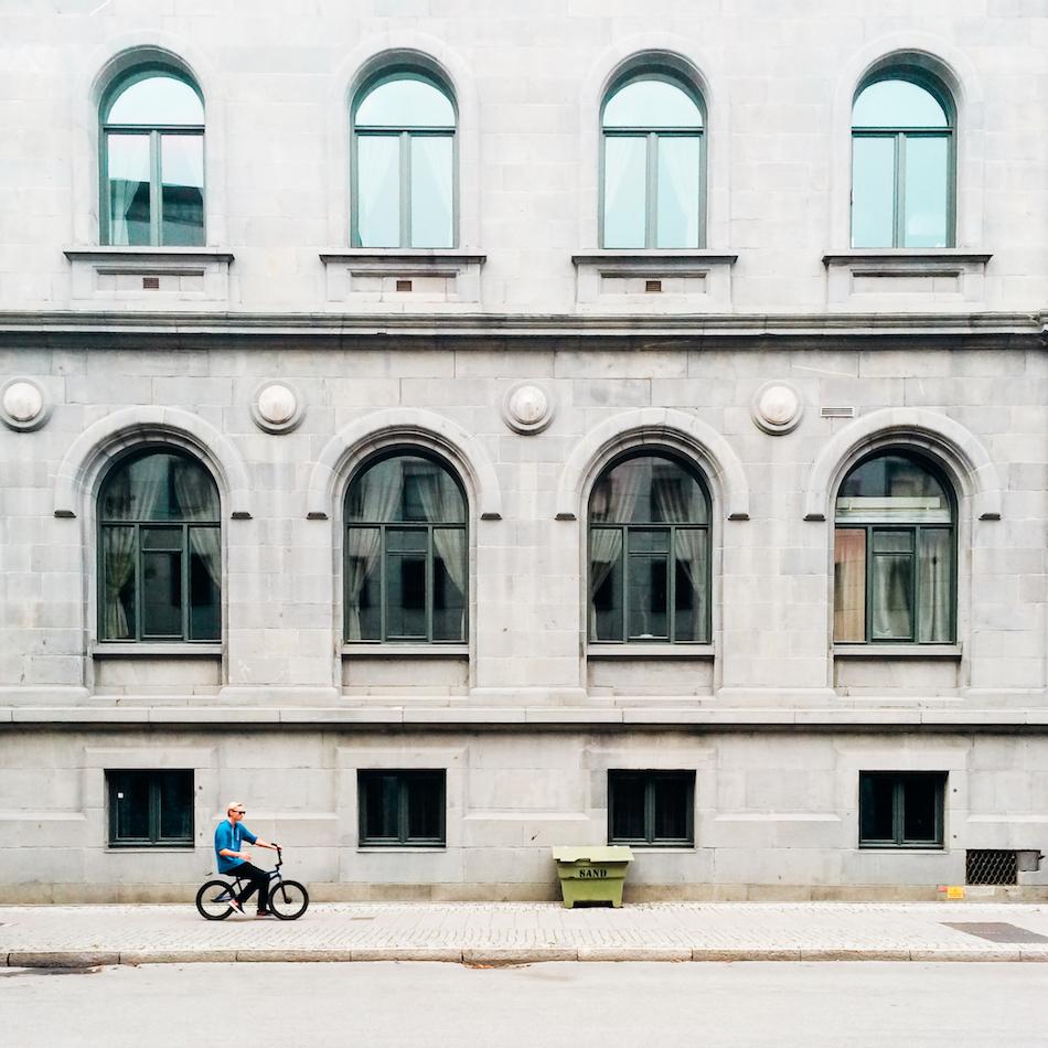 '' Small wheels keep on turning '' - Jeg liker å fotografere fasader, og denne trengte et menneskelig element for å bli spennende. Jeg har tatt bilder av fasaden mange ganger, men rett person har liksom ikke gått forbi. Syntes det passet seg ganske bra da denne raffe syklisten trillet forbi.
