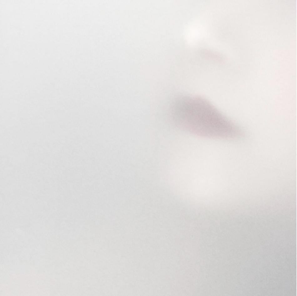 Det unge og vakre ansiktet blir skjult bak frosset glass. Med dette naturlige filteret skilles det personlige fra det private. Detaljene forsvinner og det mest fremtredende beholdes.